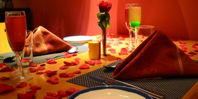 An idea for a perfect candle light dinner conglomerates dim lights, sparking candles, fresh flowers and subtle balloons.
