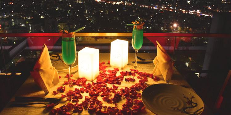 Open deck elegant dinner table adorned with subtle rose petals, and glimmer candles - Kolkata
