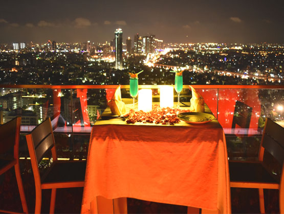 Open deck elegant dinner table adorned with subtle rose petals, and glimmer candles - Kolkata