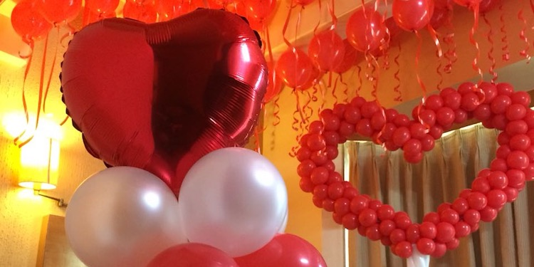 A tasteful, floral & balloon, romantic set-up of your room to surprise your loved one